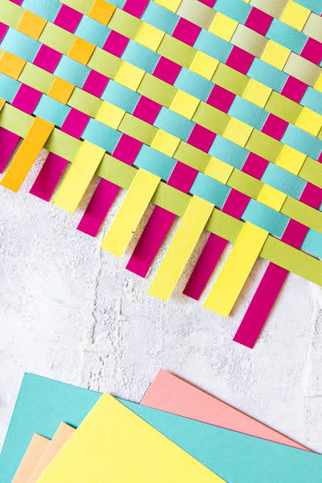 coloured strips of paper are threaded together to make a weaving pattern